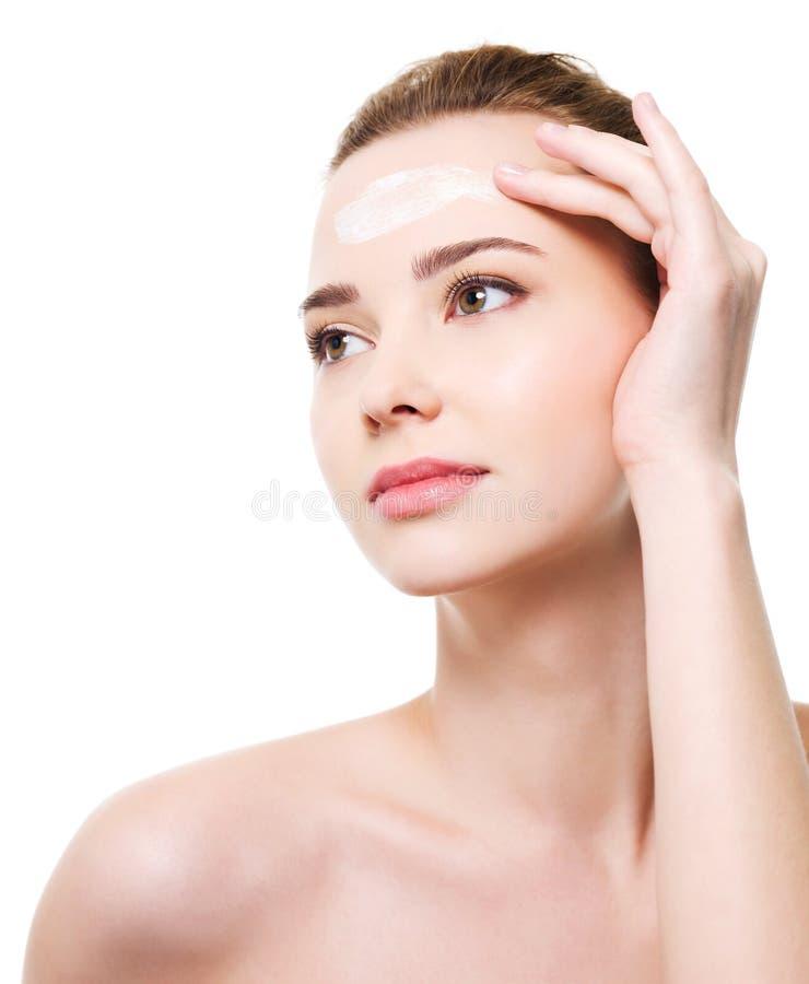 Femme appliquant le produit de beauté de crème hydratante sur le front photographie stock libre de droits
