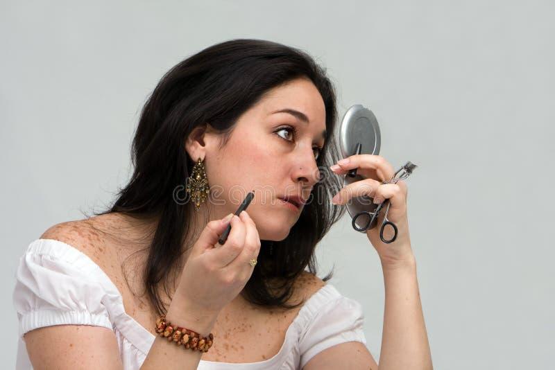 Femme appliquant le renivellement photos stock