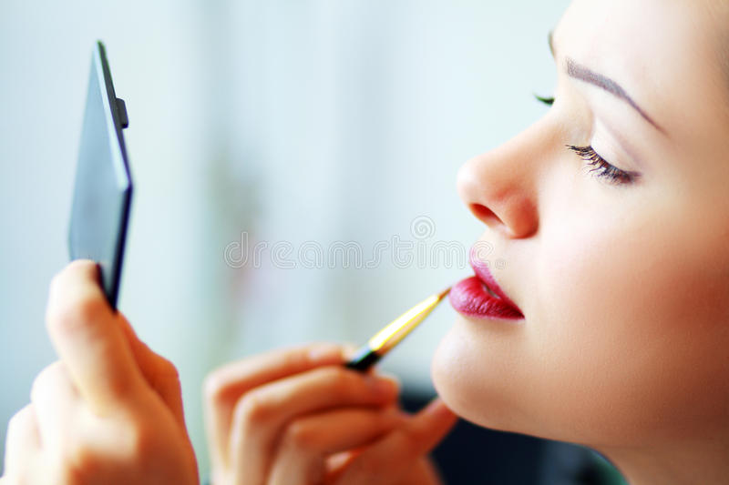 Femme appliquant le maquillage photo stock