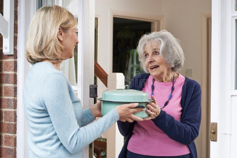 Femme apportant le repas pour le voisin plus âgé images libres de droits