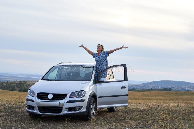 Femme appréciant avec des mains augmentées hors de la voiture, sur la route de campagne photographie stock