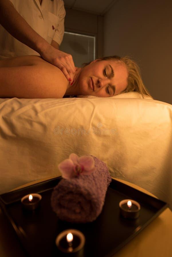 Femme appréciant détendant le massage arrière au centre cosmétique de station thermale photo libre de droits