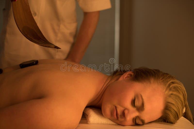 Femme appréciant détendant le massage arrière au centre cosmétique de station thermale image libre de droits