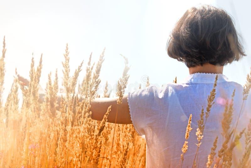 Femme appréciant dans la haute herbe image libre de droits
