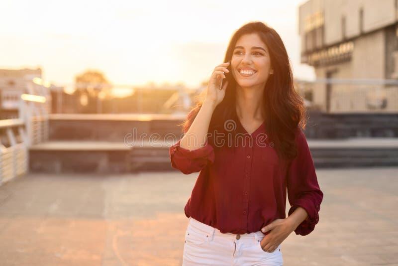 Femme appréciant l'entretien de téléphone dehors, marchant dans la ville photo stock