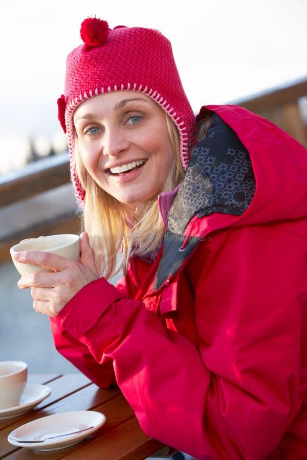 Femme appréciant la boisson chaude en café à la station de sports d'hiver photos libres de droits