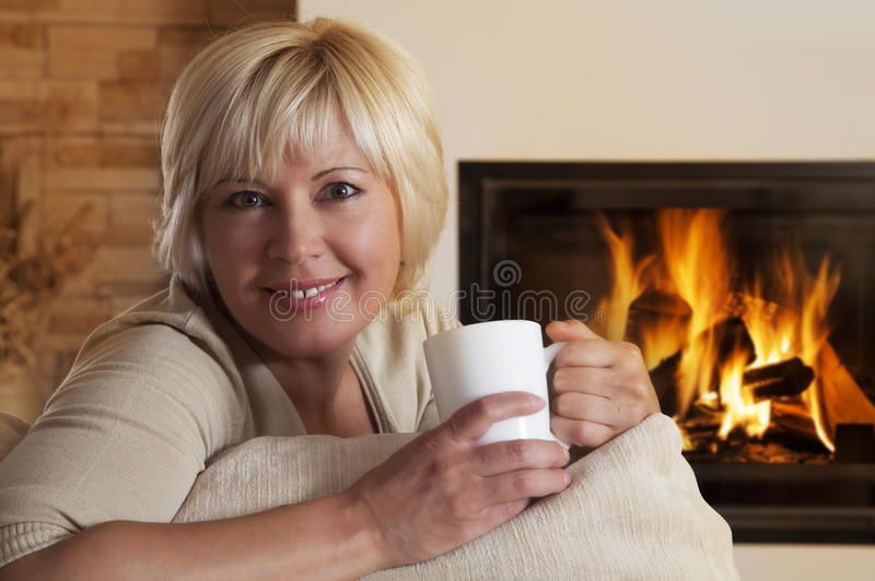 Femme appréciant la boisson chaude par la cheminée à la maison photos libres de droits