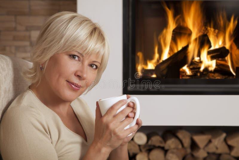 Femme appréciant la boisson chaude près de la cheminée à la maison photo libre de droits