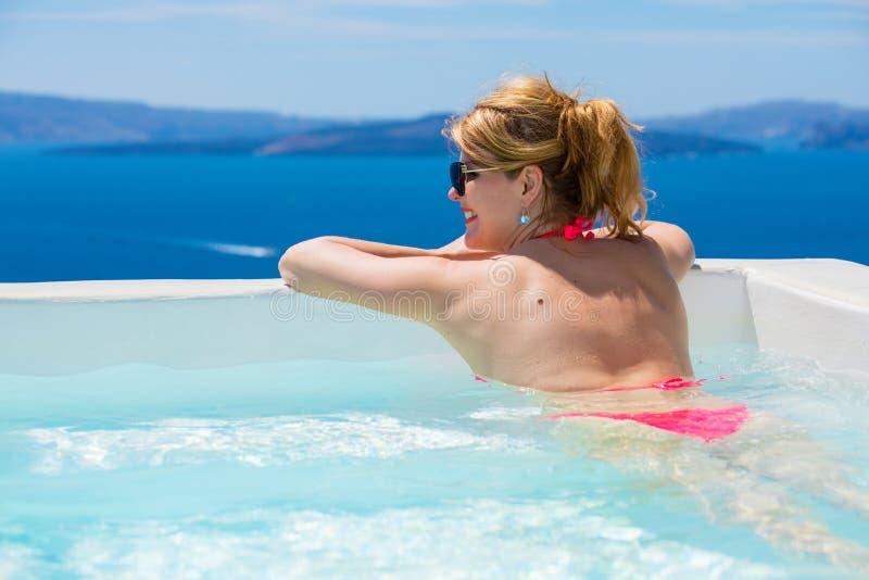 Femme appréciant la relaxation dans la piscine images stock