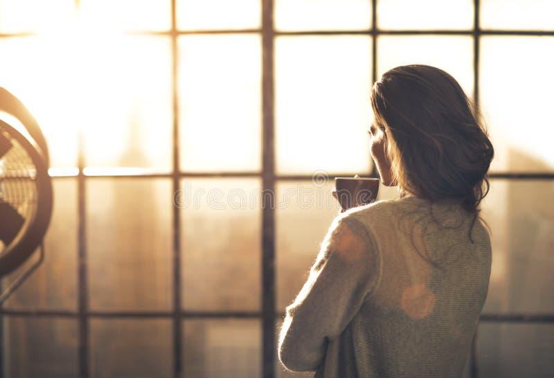 Femme appréciant la tasse de café en appartement de grenier photos libres de droits