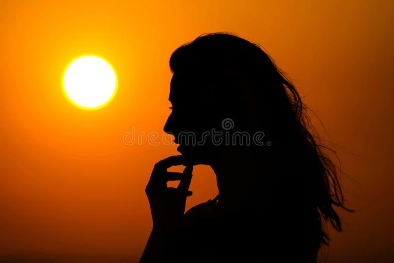 Femme appréciant le coucher du soleil photographie stock