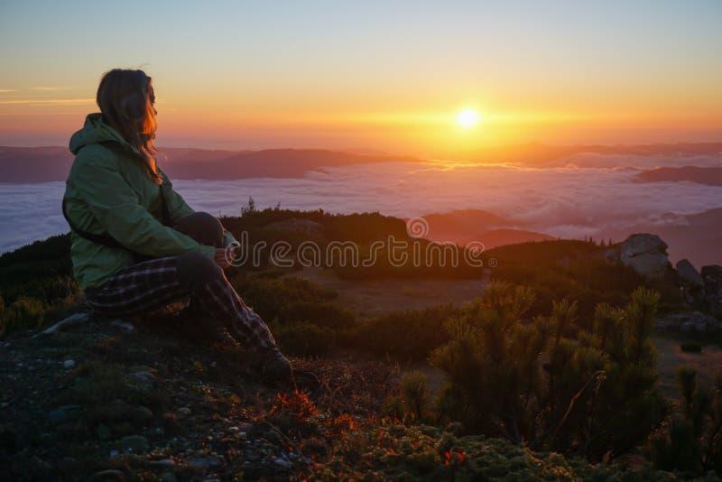 Femme appréciant le lever de soleil dans les montagnes image stock