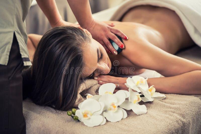 Femme appréciant les effets thérapeutiques d'un ston chaud traditionnel photos libres de droits
