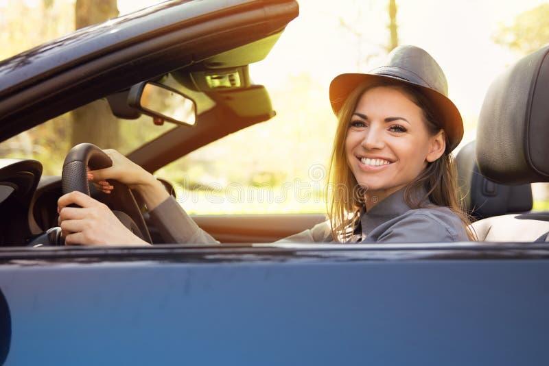 Femme appréciant une commande dans un convertible par un parc photographie stock libre de droits