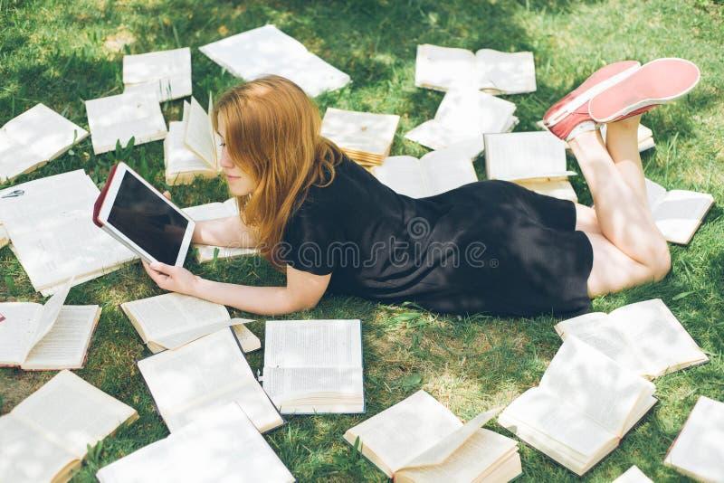 Femme apprenant avec le lecteur et le livre d'ebook Choix entre la technologie éducative moderne et la méthode traditionnelle de  images libres de droits