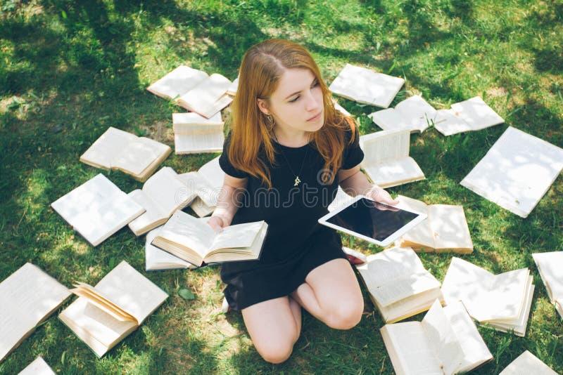 Femme apprenant avec le lecteur et le livre d'ebook Choix entre la technologie éducative moderne et la méthode traditionnelle de  photographie stock libre de droits