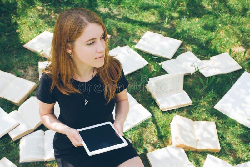 Femme apprenant avec le lecteur et le livre d'ebook Choix entre la technologie éducative moderne et la méthode traditionnelle de  photos stock