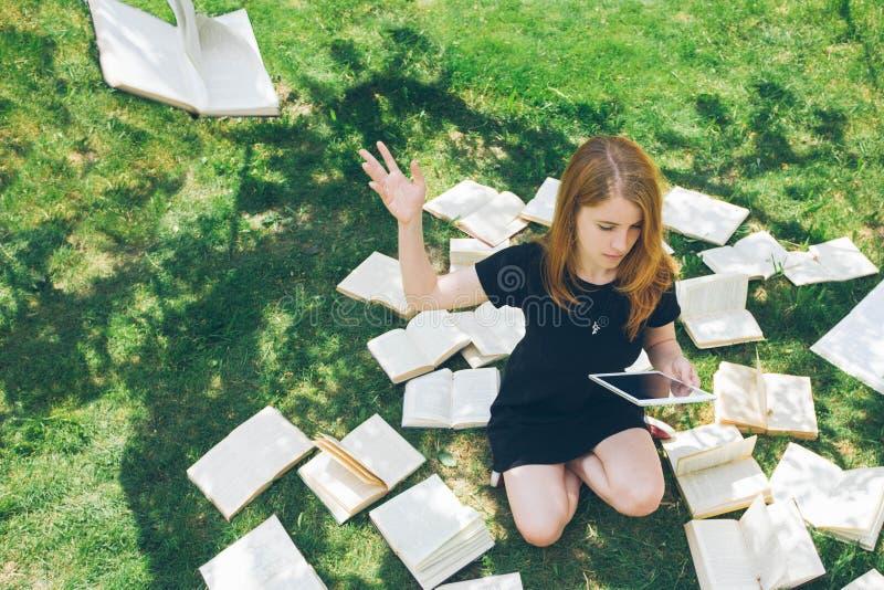 Femme apprenant avec le lecteur et le livre d'ebook Choix entre la technologie éducative moderne et la méthode traditionnelle de  images stock