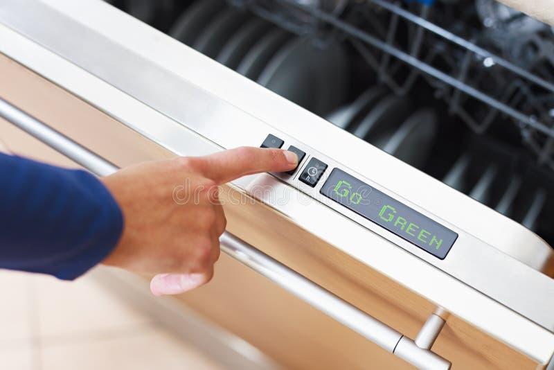 Femme appuyant sur le bouton d'épargnant d'énergie sur le lave-vaisselle images libres de droits