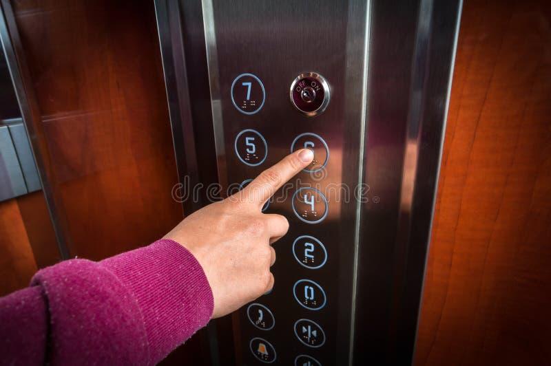 Femme appuyant sur le bouton dans l'intérieur d'ascenseur photo stock