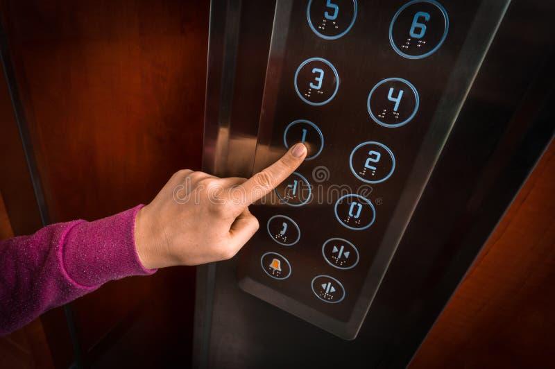 Femme appuyant sur le bouton dans l'intérieur d'ascenseur image libre de droits