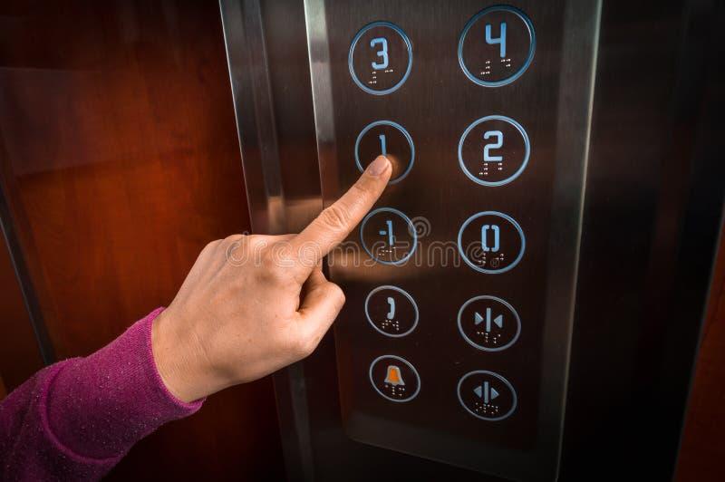 Femme appuyant sur le bouton dans l'intérieur d'ascenseur images libres de droits