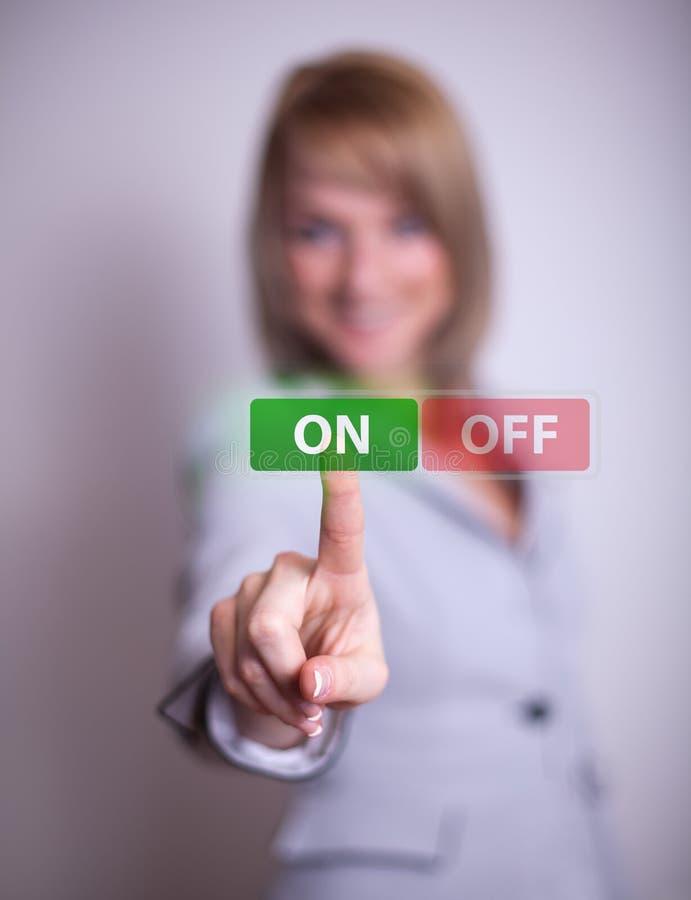 Femme appuyant sur le bouton 'MARCHE/ARRÊT' photos stock