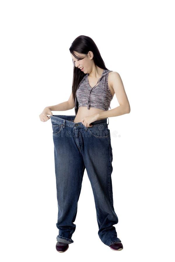 Femme après la perte de poids essayant ses vieux jeans photo stock