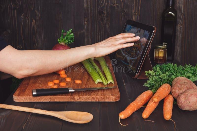 Femme après recette sur le comprimé et faire cuire le repas sain dans la cuisine, coupant des légumes sur la table en bois photo stock