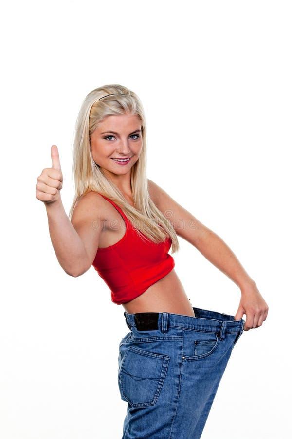 Femme après un régime réussi avec de grands pantalons images stock