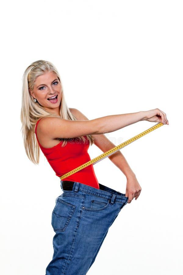 Femme après un régime réussi avec de grands pantalons image libre de droits