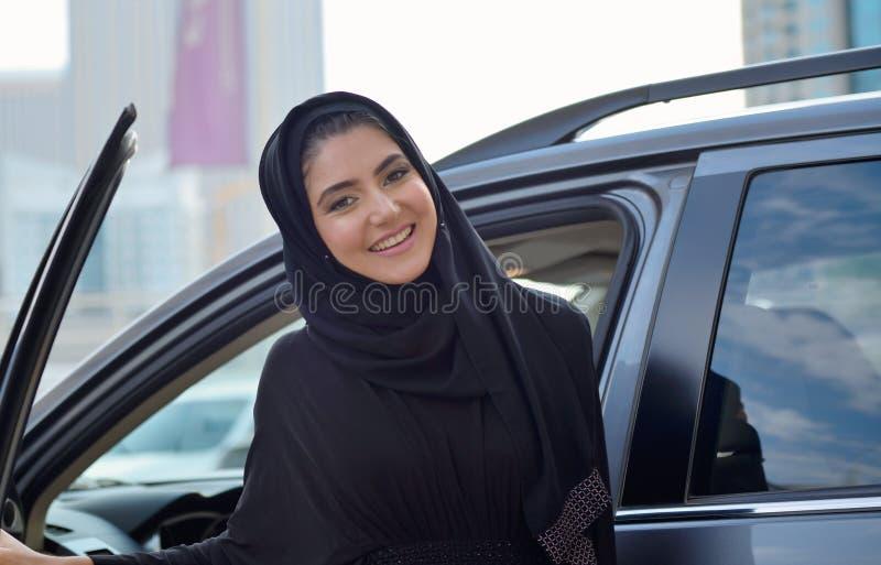 Femme arabe d'affaires d'Emarati obtenant à l'intérieur de la voiture image libre de droits
