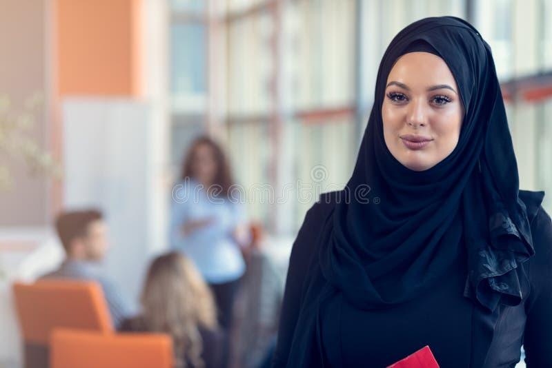 Femme Arabe d'affaires tenant un dossier dans le bureau de démarrage moderne image stock
