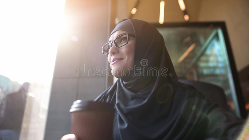 Femme arabe dans des lunettes regardant la rue de ville, café de détente avec la tasse de thé images stock
