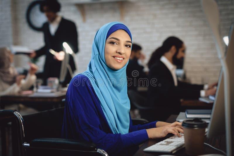 Femme arabe handicapée dans le fauteuil roulant fonctionnant dans le bureau La femme travaille sur l'ordinateur de bureau image libre de droits