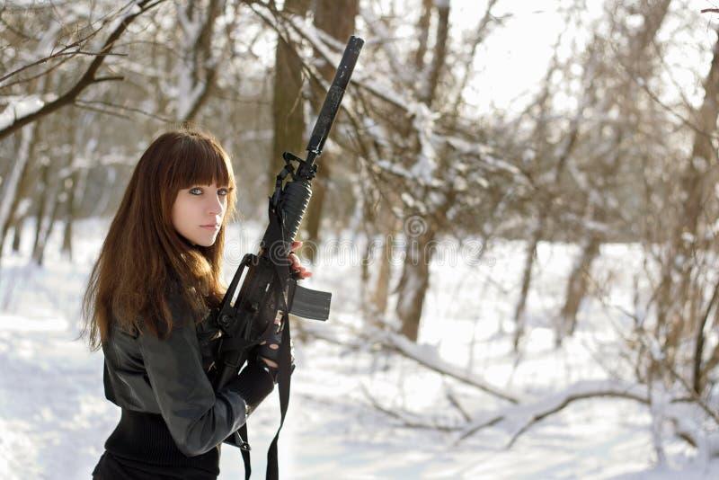 Femme armée dans la forêt de l'hiver image stock