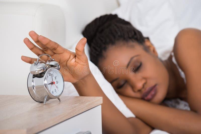 Femme arrêtant l'alarme tout en dormant sur le lit photos libres de droits