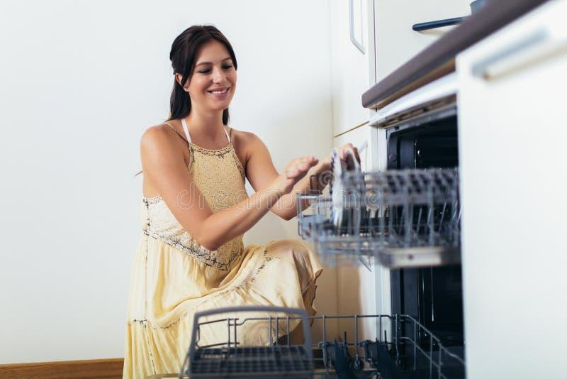 Femme arrangeant des plats dans le lave-vaisselle At Home photo stock