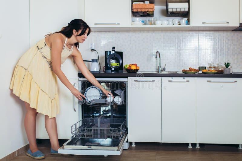Femme arrangeant des plats dans le lave-vaisselle At Home photos libres de droits