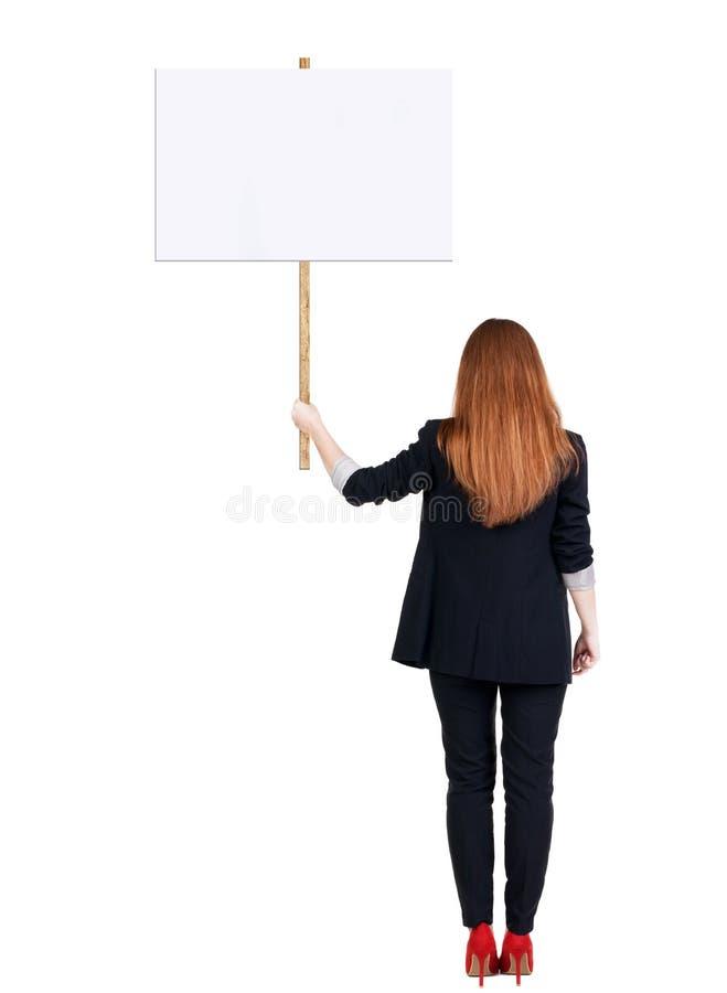 Femme arrière d'affaires de vue montrant le panneau de signe photo stock