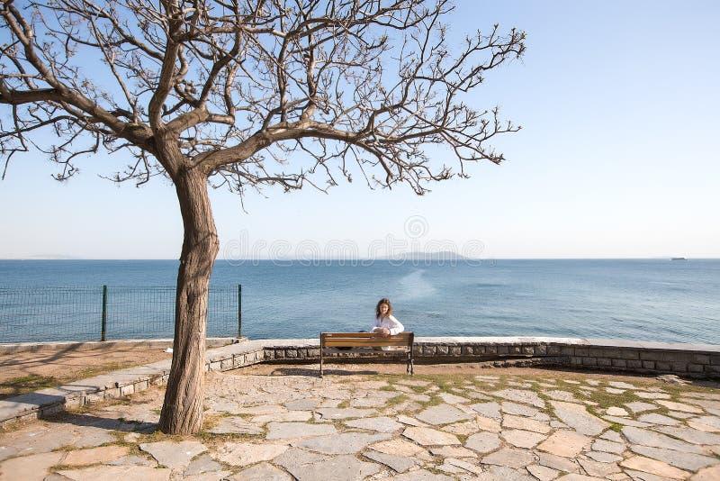Femme arrière de portrait s'asseyant sur un banc à la mer vue étonnante, fille avec les cheveux bouclés, femme dans la chemise bl image libre de droits