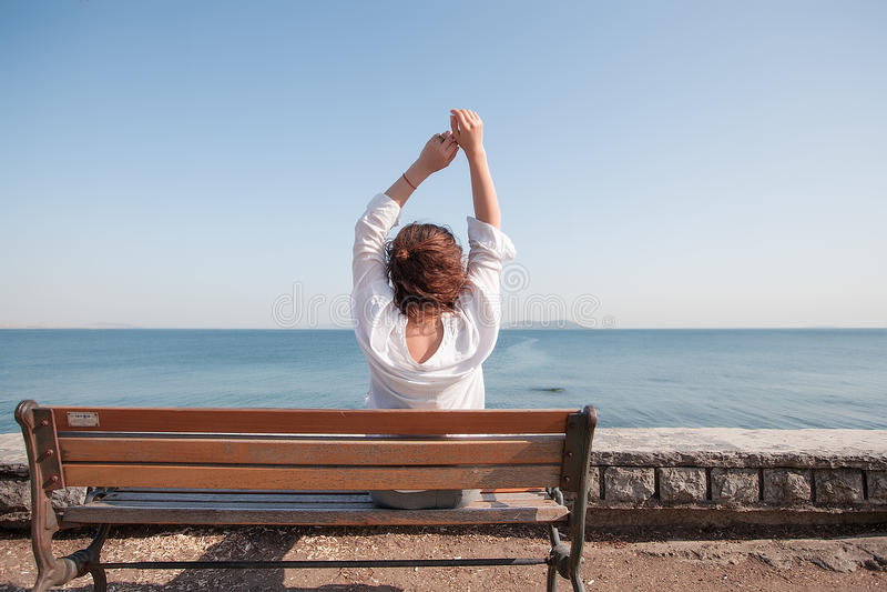 Femme arrière de portrait s'asseyant sur un banc à la mer vue étonnante, fille avec les cheveux bouclés, femme dans la chemise bl photos stock