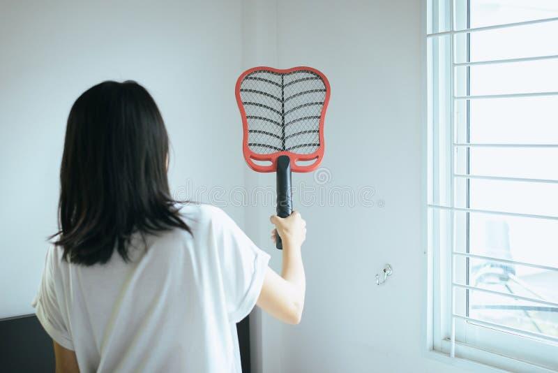 Femme asiatique à l'aide de la tapette de moustique à la maison, femelle avec la raquette nette électrique de moustique dans la c image stock