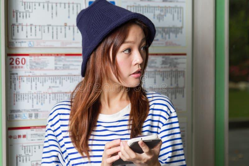 Femme asiatique à l'arrêt d'autobus photo libre de droits