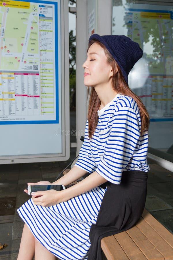 Femme asiatique à l'arrêt d'autobus photographie stock libre de droits