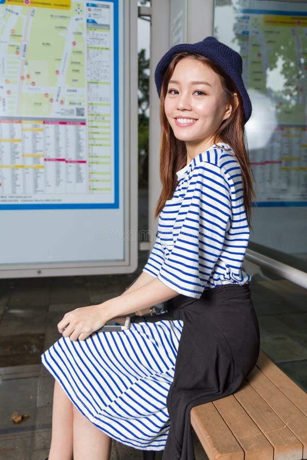 Femme asiatique à l'arrêt d'autobus photographie stock