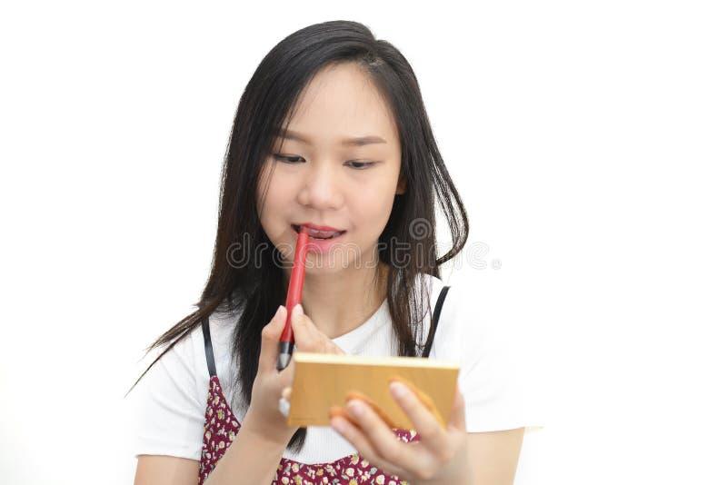 Femme asiatique appliquant le rouge à lèvres rouge avec le crayon cosmétique image libre de droits