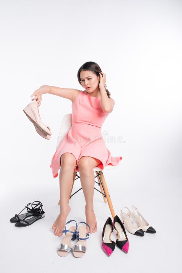 Femme asiatique assez jeune ayant le choix difficile pour essayer quelques uns photo stock