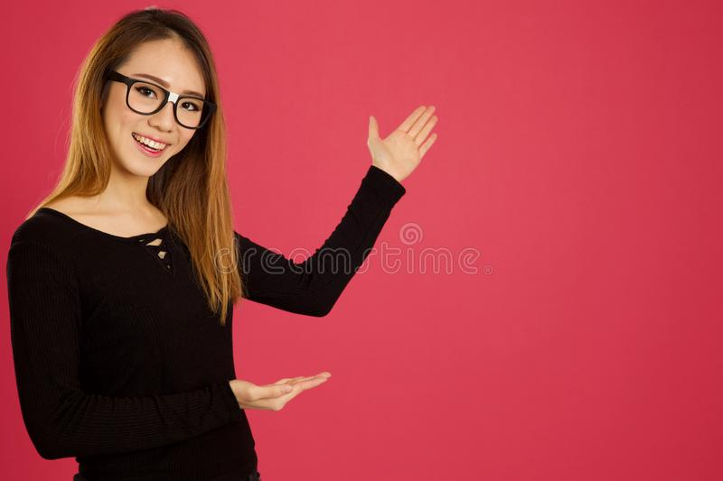 Femme asiatique assez jeune dans le studio se dirigeant avec les deux mains image stock