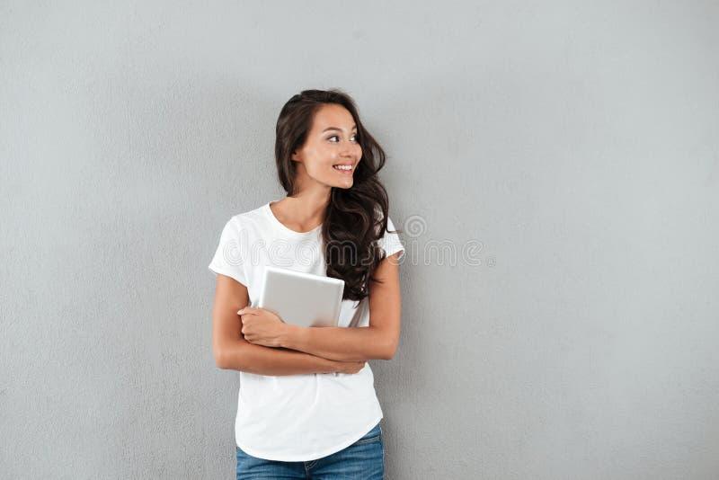 Femme asiatique assez jeune tenant la tablette photos stock